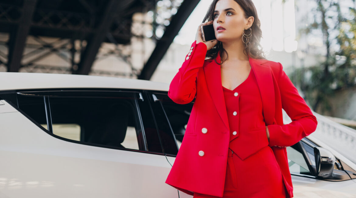 beautiful sexy woman in red suit posing at car talking on business on phone