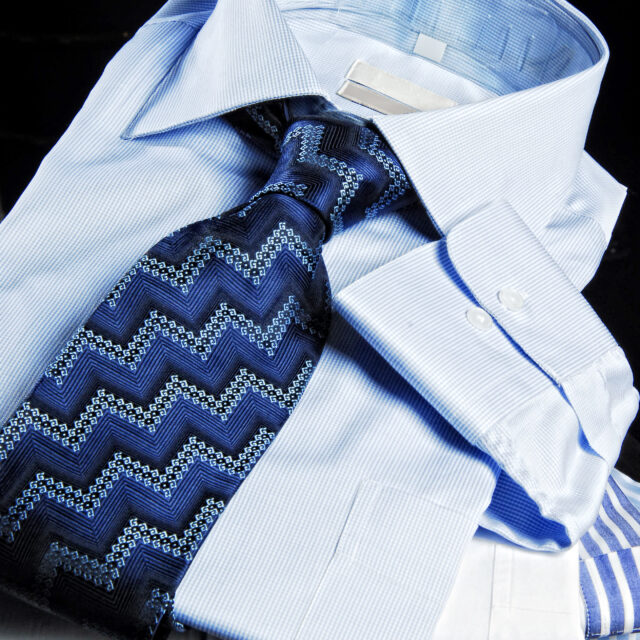 Folded shirts with tie on the black background.